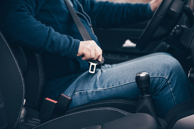 Passenger  senior man fastening seat belt in the car, transport and  safety concept
