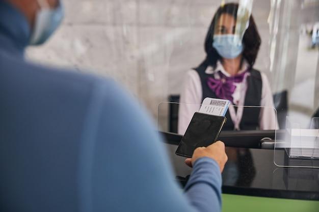 검은 머리 공항 직원에게 여행 서류를 보여주는 승객