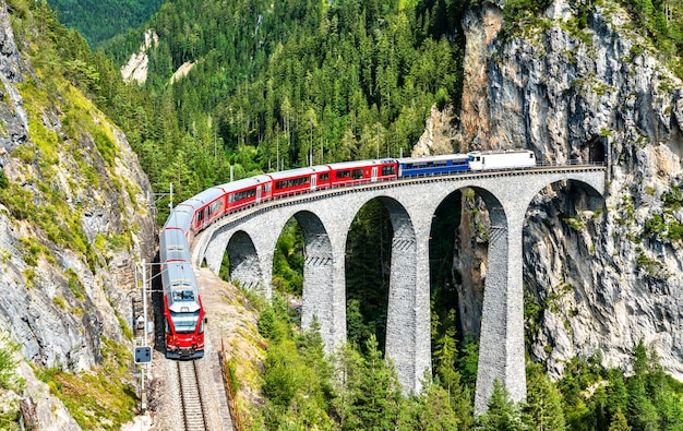 Passenger train crossing the landwasser viaduct in the swiss alps
