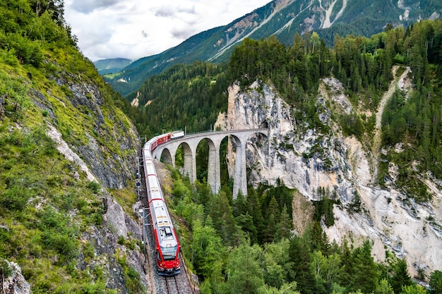 Passenger train crossing the landwasser viaduct in switzerland
