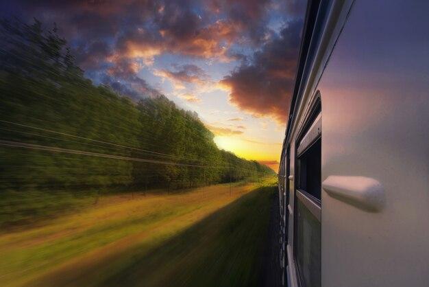 日没時に森の中でぼかし効果で動いている旅客列車。