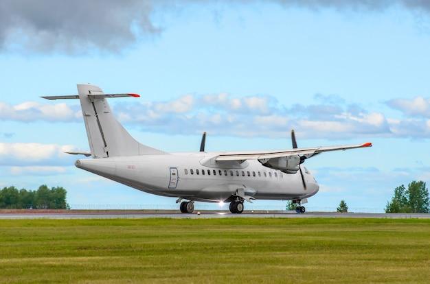 Passenger turboprop airplane landing the runway against the blue sky.