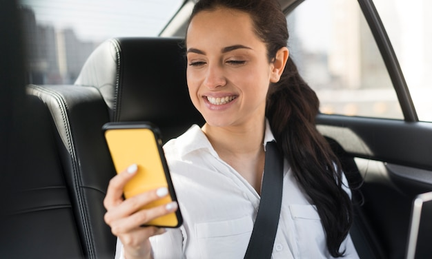 Passenger using her mobile phone in the car