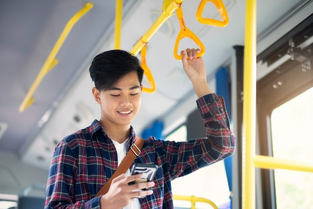 The passenger using mobile phone on the public bus.