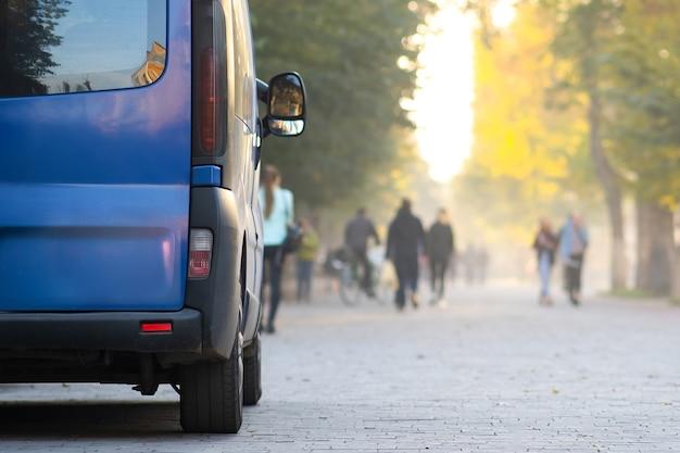 Пассажирский фургон, припаркованный на обочине городской аллеи с размытыми идущими пешеходами осенью.