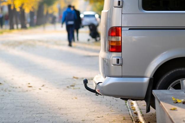 Пассажирский фургон припаркован на обочине городской аллеи с размытыми идущими пешеходами осенью.