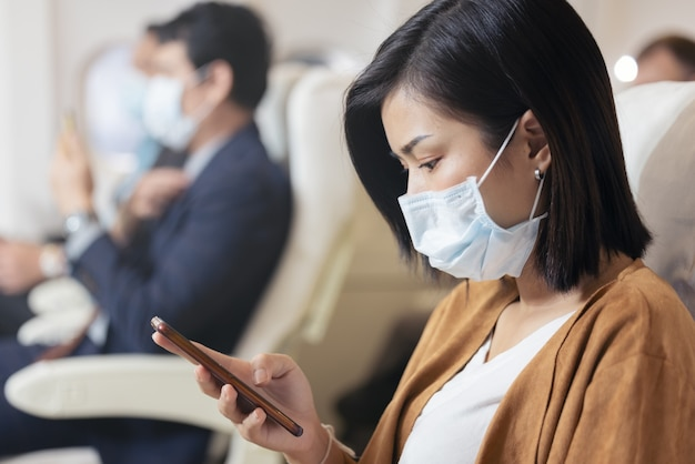 Passenger wearing face mask using mobile phone on airplane during covid pandemic to prevent coronavirus infection