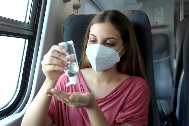 Пассажир в защитной маске дезинфицирует руки в общественном транспорте