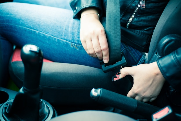 Passenger woman fastening seat belt in the car, safety concept