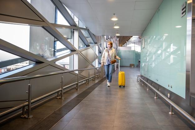 거의 공항에서 그녀의 짐을 걷고 코로나 바이러스 걷기를 방지하기 위해 의료 보호 마스크를 착용하는 승객 여자