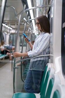 地下鉄の電車の中でソーシャルネットワークでチャットをしている携帯スマートフォンを使用している乗客の若い女性