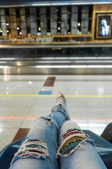 Passengers are waiting for their flight in the airport waiting area. first-person view, girl in ripped jeans