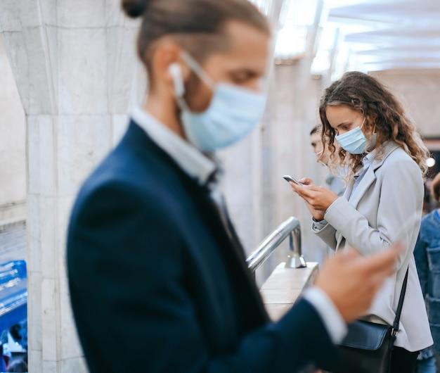 지하철 건널목에서 보호 마스크를 착용 한 승객