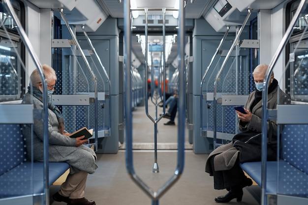 地下鉄車両に座っている保護マスクの乗客
