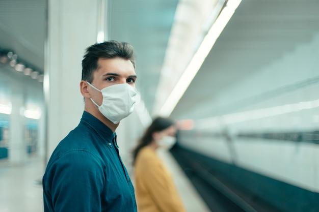 안전한 거리에 있는 지하철역에 서 있는 보호 마스크를 쓴 승객. 도시의 코로나바이러스