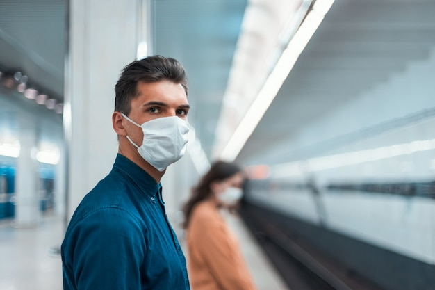 安全な距離にある地下鉄の駅に立っている保護マスクの乗客