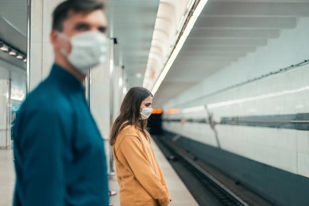 지하철 역에 서 있는 보호 마스크를 쓴 승객. 도시의 코로나바이러스
