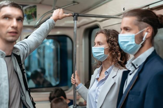 지하철로 여행하는 보호 마스크를 착용 한 승객