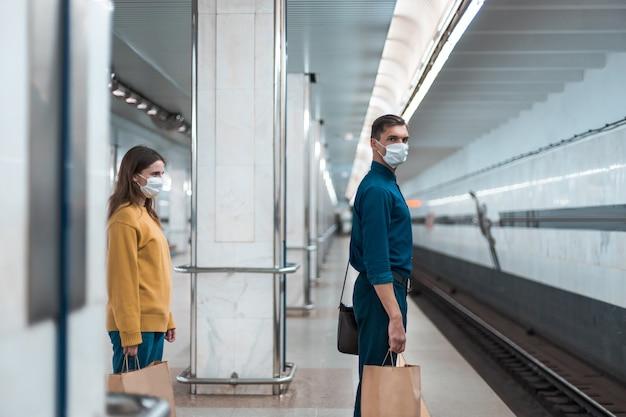 보호 마스크를 착용한 승객들이 지하철을 기다리고 있습니다. 도시의 코로나바이러스