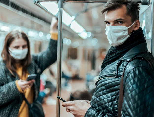 Passengers in protective masks standing in the subway car. coronavirus in the city