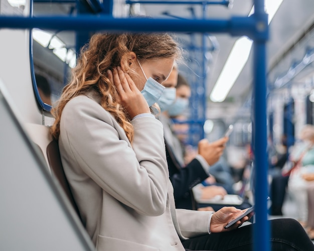 Passengers in protective masks using their gadgets in the subway car