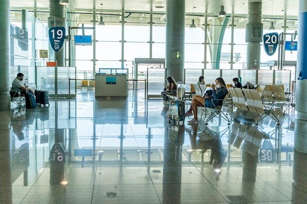 Пассажиры, ожидающие в зоне посадки в аэропорту, в зале ожидания, в масках