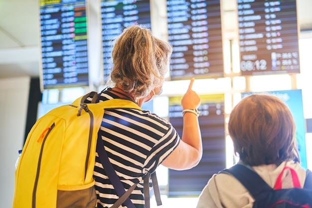 Пассажиры с рюкзаком и чемоданами смотрят на табло вылета в терминале аэропорта