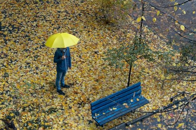 雨の秋の日に傘をさして通りを通り過ぎる通行人。上面図。