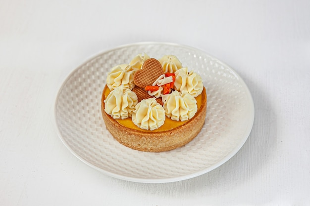 Passion fruit cake and mango on top with a round cream on a round white plate on a white  isolated