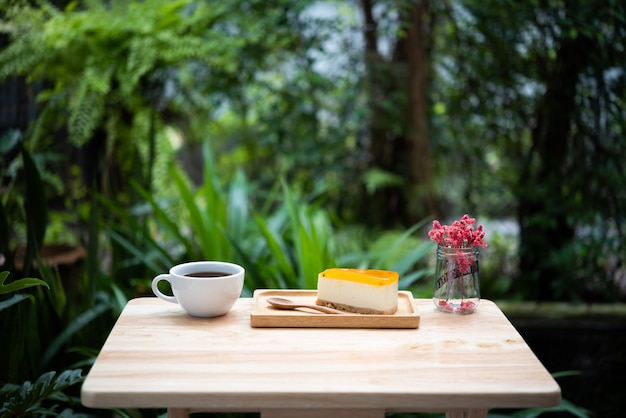 Passion fruit cheesecake and hot coffee cup on wooden tray and table