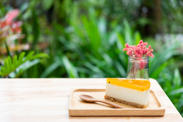 Passion fruit cheesecake serve on wood tay and wooden table with dried flower vase