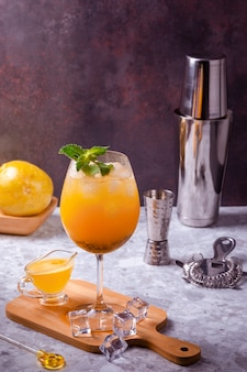 パッションフルーツカクテルは、キッチンボードのワイングラスで提供され、床にはいくつかの角氷があり、底はパッションフルーツ全体、カクテルシェーカー、ストレーナー、ドーサーで構成されています。コピースペース