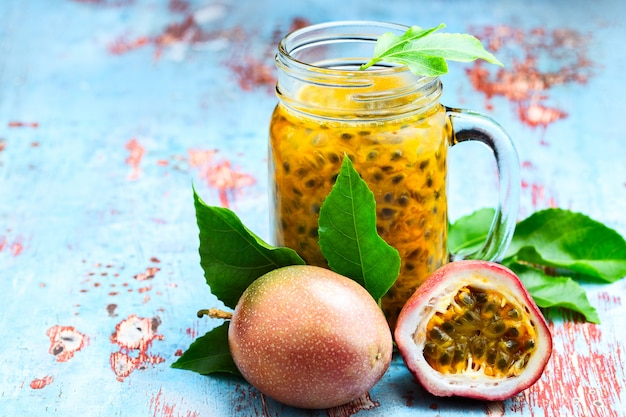 Passion fruit in a glass jar with whole and half fruit on blue wooden table