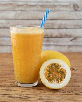 木製のテーブルの上にフルーツとグラスのパッションフルーツジュース。