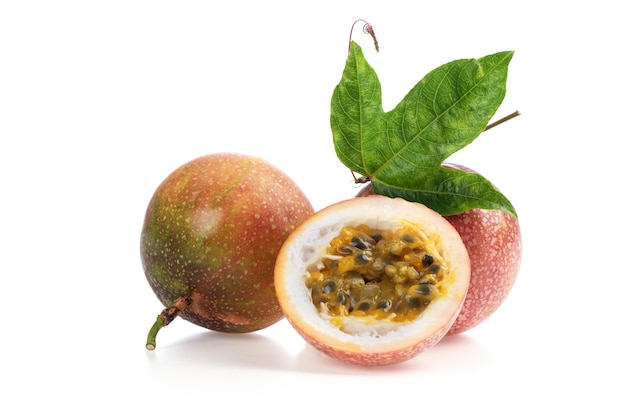 Passion fruit or passiflora edulis fruits and green leaves isolated on white background.