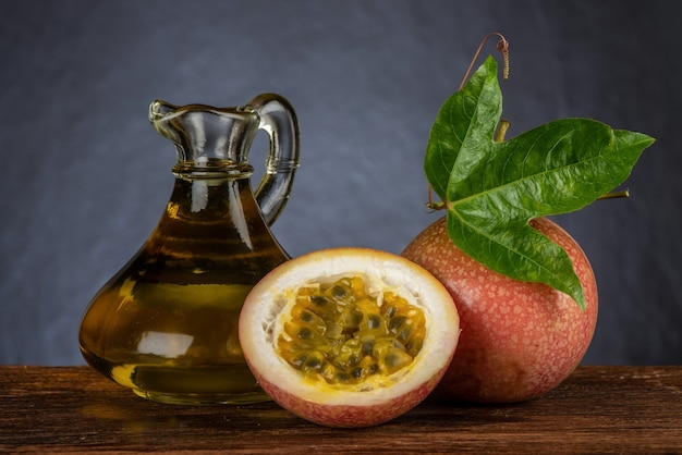 Passion fruit or passiflora edulis fruits and oil on an old wood background.