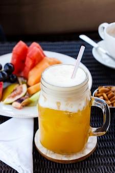 Страстный пунш коктейль. освежающий напиток из тропического коктейля из маракуйи в стеклянной банке. орехи, арахис, капучино и фрукты.