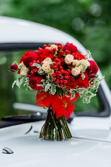 Passion wedding bouquet with dark red and marsala roses, greenery standing on white car