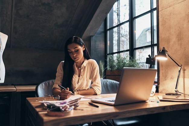 彼女の仕事に情熱を注いでいます。彼女のワークショップに座ってスケッチに取り組んでいる美しい若い女性