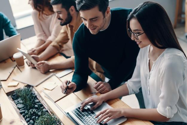 彼らのプロジェクトに情熱を注いでいます。クリエイティブオフィスで働いている間、現代の技術を使用してスマートカジュアルウェアの若い現代人の上面図