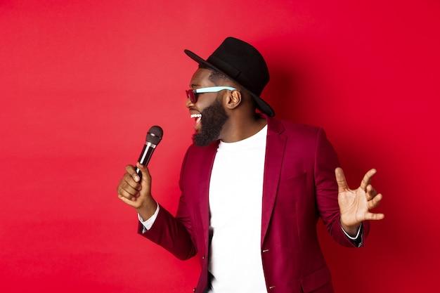 Страстный черный певец, выступающий на красном фоне, поющий в микрофон, одетый в праздничный костюм, стоит на красном фоне.