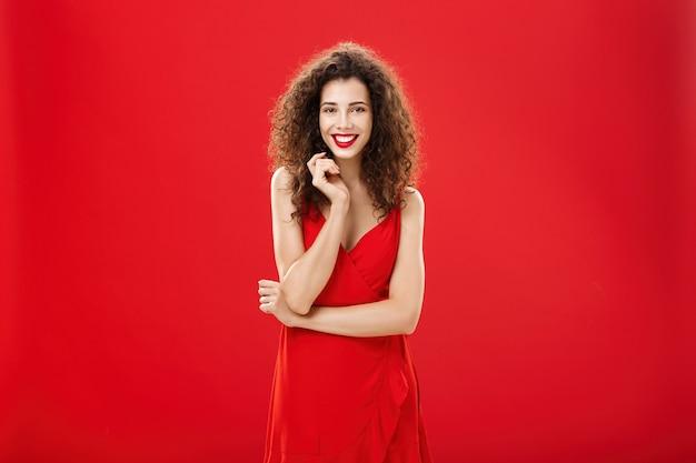 빨간 배경 위에 열정적인 매력적인 유럽 여성이 곱슬머리를 한 우아한 드레스를 입고 소심하고 어리석은 머리카락을 가지고 노는 귀엽고 여성스러운 미소를 지으며 자신이 존경하는 사람과 이야기합니다.