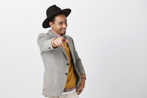 Passionate confident dark-skinned male choosing you. portrait of charming african-american in fashionable hat and jacket, pulling hand and pointing with sensual flirty smile over gray wall