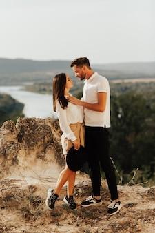 Страстная пара с любовью смотрят друг на друга. влюбленные люди, стоящие на горе.
