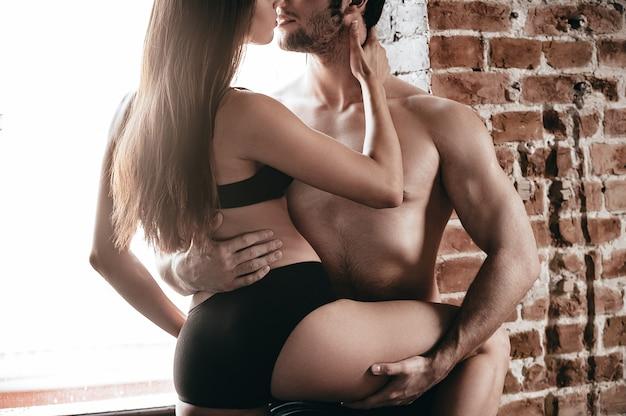 情熱的なカップル。窓枠に寄りかかって抱き合ったりキスしたりする美しい若い上半身裸のカップルのクローズアップ部分