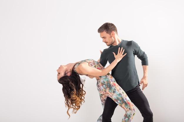 白い壁にラテンダンスを踊る情熱的なカップル