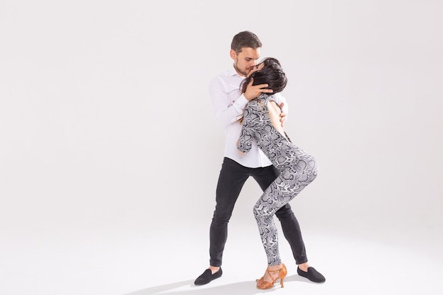 복사 공간이 있는 흰색 배경에서 사교 댄스 키좀바, 바차타, 셈바 또는 타락시아를 춤추는 열정적인 커플