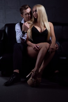 Passionate couple in elegant evening dresses embrace on a black leather sofa
