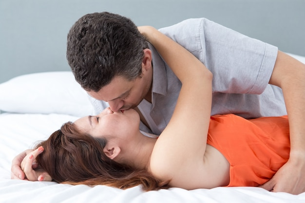 Passionate couple embracing and kissing in bed