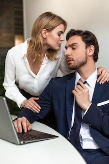 열정적 인 커플이 사무실에서 바람둥이. 사업가 직장 근처에 서있는 동안 뒤에서 그를 만지고 여자에 보인다. 유혹 개념.